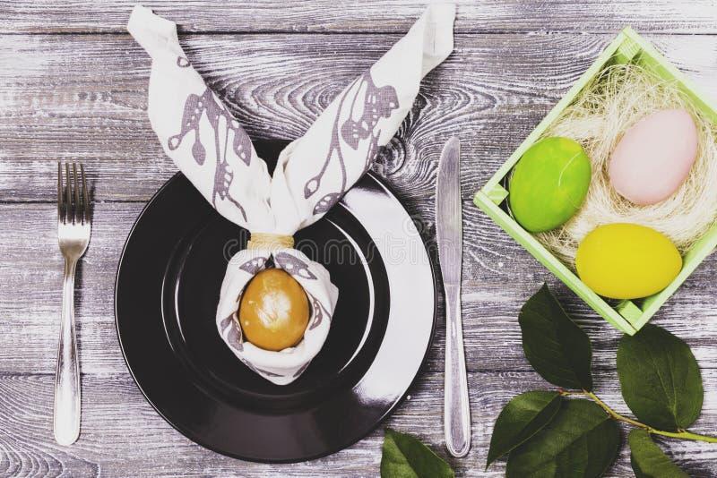 Hoogste die mening van een paasei in een servet in de vorm van konijnoren wordt verpakt op een zwart plaat en een bestek, kleurri stock foto's