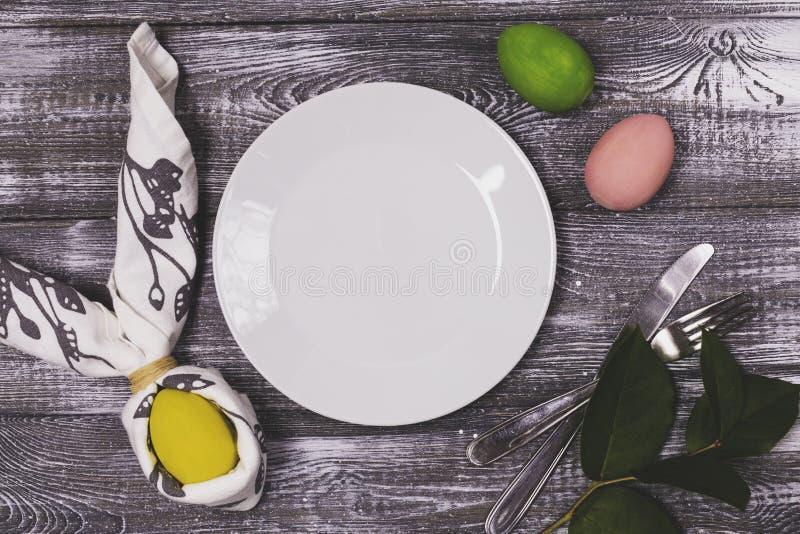 Hoogste die mening van een paasei in een servet in de vorm van konijnoren wordt verpakt, een wit plaat en een bestek, kleurrijke  stock afbeeldingen