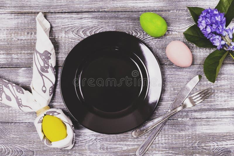 Hoogste die mening van een paasei in een servet in de vorm van konijnoren wordt verpakt, een zwart plaat en een bestek, kleurrijk royalty-vrije stock afbeelding