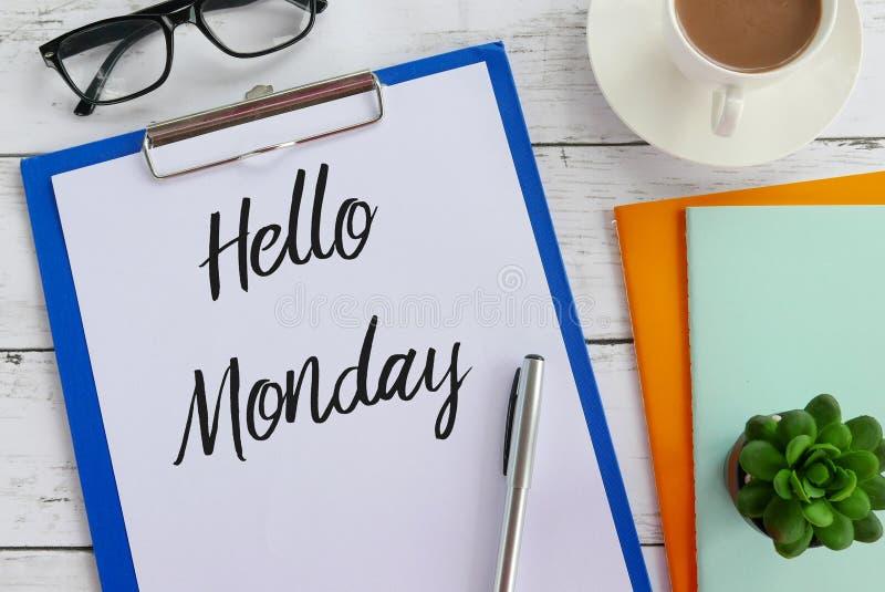 Hoogste die mening van glazen, koffie, installatie, notitieboekje, pen, klembord en document met Hello-Maandag worden geschreven royalty-vrije stock fotografie