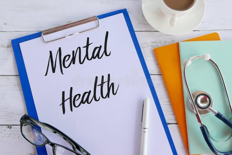 Hoogste die mening van koffie, boeken, stethoscoop, glazen, pen, klembord, en document met Geestelijke Gezondheid wordt geschreve stock afbeelding