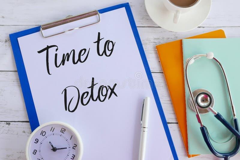 Hoogste die mening van koffie, boeken, stethoscoop, klok, klembord en document met Tijd aan Detox wordt geschreven stock foto