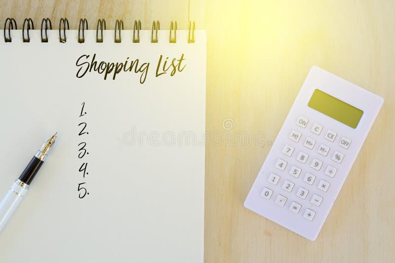 Hoogste die mening van pen, calculator en notitieboekje met het Winkelen Lijst op houten achtergrond wordt geschreven stock fotografie