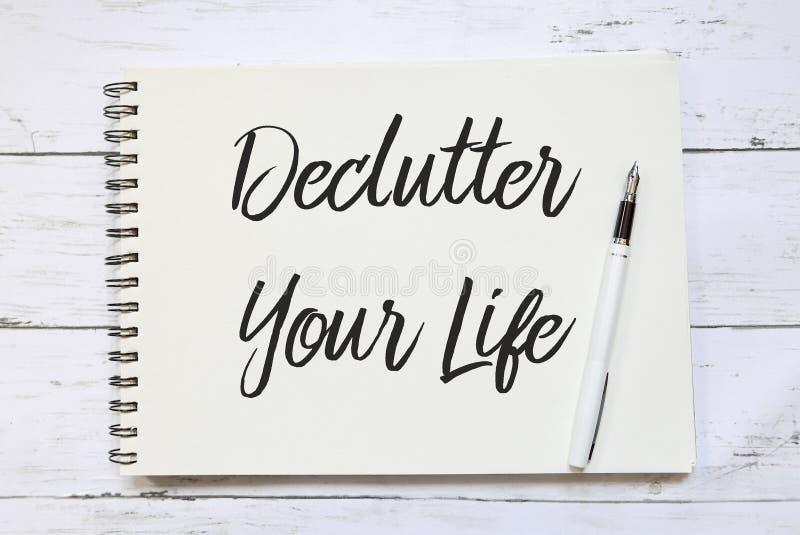Hoogste die mening van pen en notitieboekje met Declutter Uw Leven op houten achtergrond wordt geschreven stock fotografie