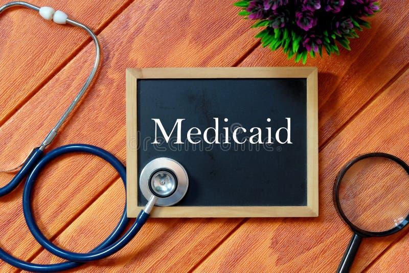 Hoogste die mening van stethoscoop, vergrootglas, installatie en bord met Medicaid op houten achtergrond wordt geschreven Het con stock foto's