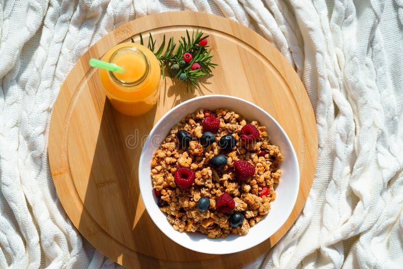 Hoogste horizontale mening over de gezonde bessen van ontbijtgranola in witte kom en verse sinaasappel juce op rond houten gebrei royalty-vrije stock afbeeldingen