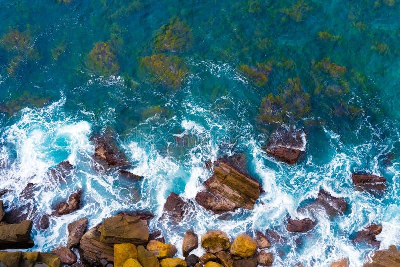 Hoogste luchtmening van blauwe golven die op rotsachtige Australische kustlijn verpletteren stock foto's
