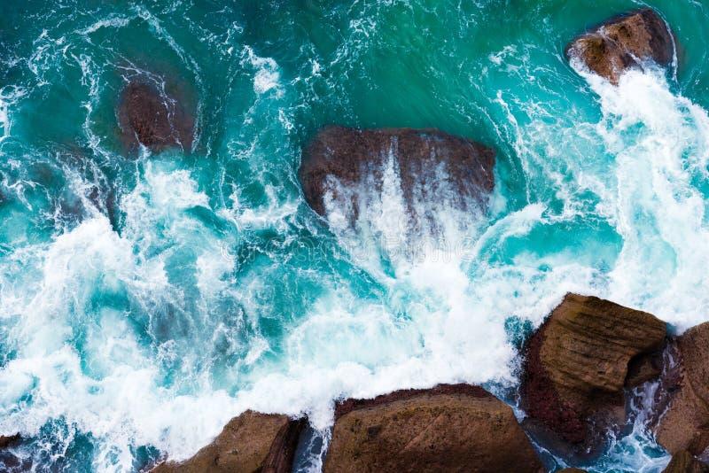 Hoogste luchtmening van blauwe golven die op rotsachtige Australische kustlijn verpletteren royalty-vrije stock foto