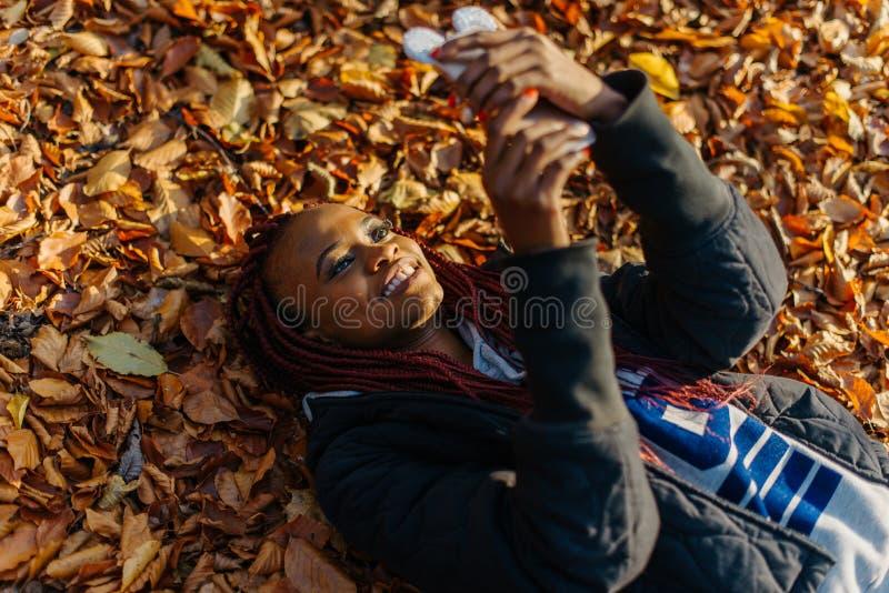 Hoogste mening bij het mooie aantrekkelijke Afrikaanse meisje met rood haar en mooie glimlach die, en op texting doorbladeren bab stock afbeelding