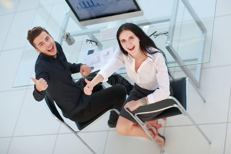Hoogste mening de bedrijfspaarzitting bij Bureau en het tonen beduimelen omhoog stock foto's