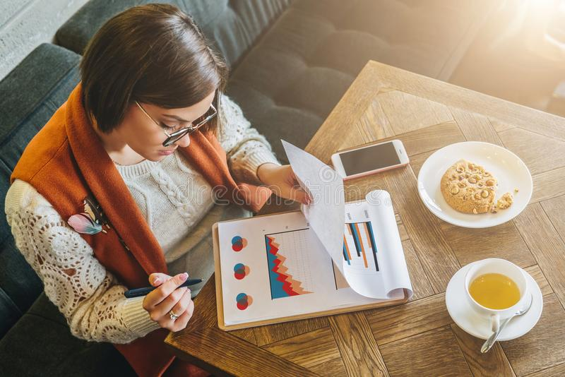 Hoogste mening De jonge aantrekkelijke vrouw, ondernemer zit in koffie bij lijst en het werken De onderneemster bekijkt grafieken stock afbeelding
