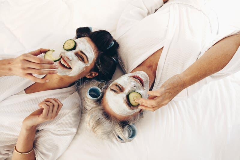 Hoogste mening die van glimlachende moeder en dochter op bed met gezicht p liggen stock afbeelding