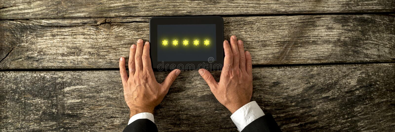 Hoogste mening die van mannelijke hand digitale tablet met vijf gouden st houden royalty-vrije stock fotografie