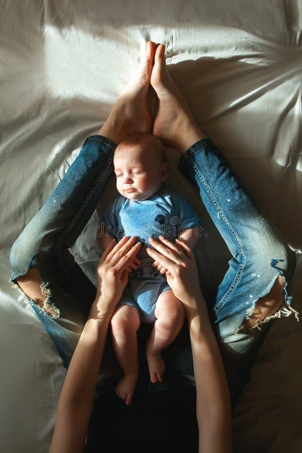 Hoogste mening die van mooi jong mamma en haar leuke kleine zoon op wit bedlinnen liggen Mamma die de handen van haar slaapbaby h royalty-vrije stock afbeeldingen