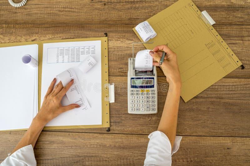 Hoogste mening die van vrouwelijke accountant berekeningen maken die toevoegend m gebruiken stock fotografie