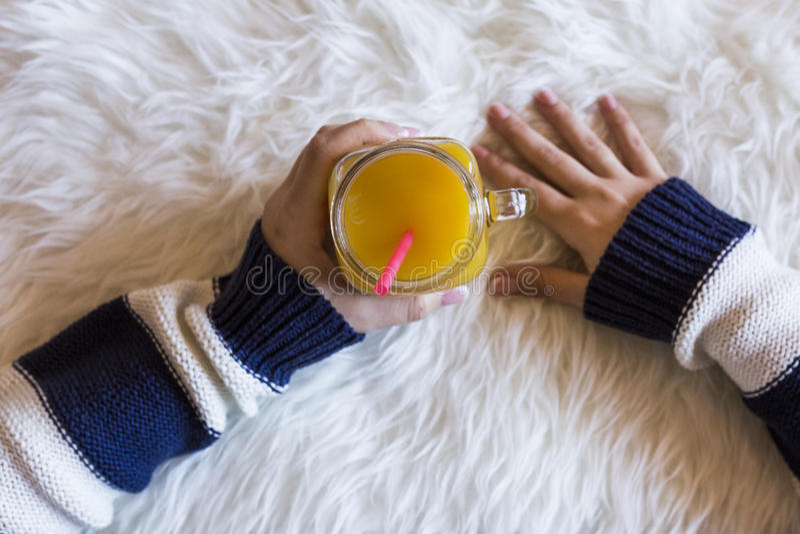 Hoogste mening die van vrouwenhanden een kruik het verfrissen van jus d'orange houden royalty-vrije stock afbeeldingen