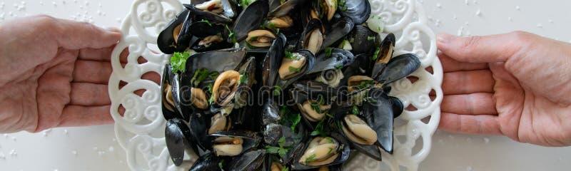 Hoogste mening die van vrouwenhanden een plaat met gekookte heerlijke zwarte mossel houden Gezond het eten concept, eiwitvoedsel royalty-vrije stock afbeeldingen