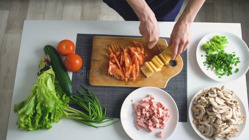 Hoogste mening die van vrouwenhanden groenten op een houten raad voor pizzadiner thuis snijden in de keuken stock foto's