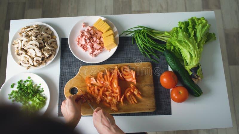 Hoogste mening die van vrouwenhanden groenten op een houten raad voor pizzadiner thuis snijden in de keuken stock foto