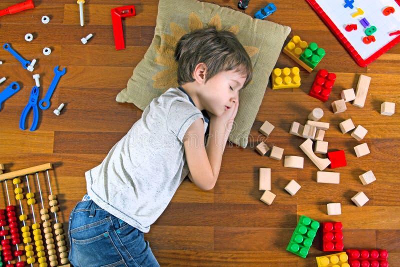 Hoogste mening die van weinig jongen met gesloten ogen op de houten vloer en veel kleurrijk speelgoed rond hem liggen stock foto