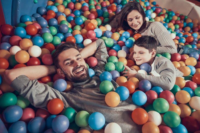 Hoogste mening Gelukkige familie die in pool met ballen liggen stock fotografie