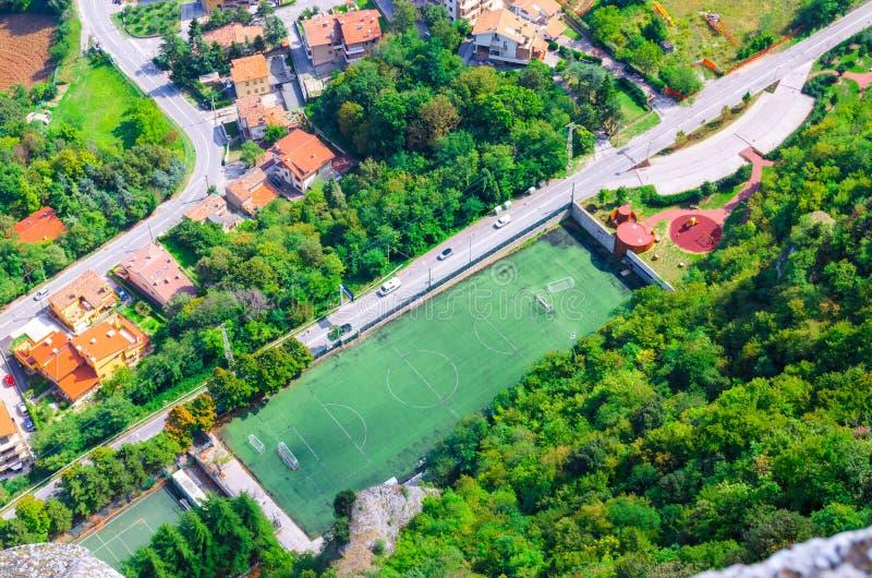 Hoogste mening hierboven van gebied van het het grasgazon van het voetbalstadion het groene en bomen, weg, huizen met oranje dake royalty-vrije stock foto