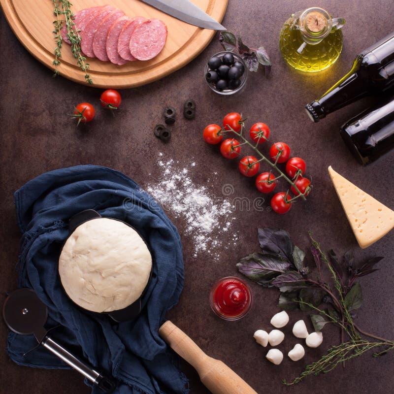 Hoogste mening Ingrediënten voor het maken van smaakvolle pepperonispizza op donkere achtergrond royalty-vrije stock foto's