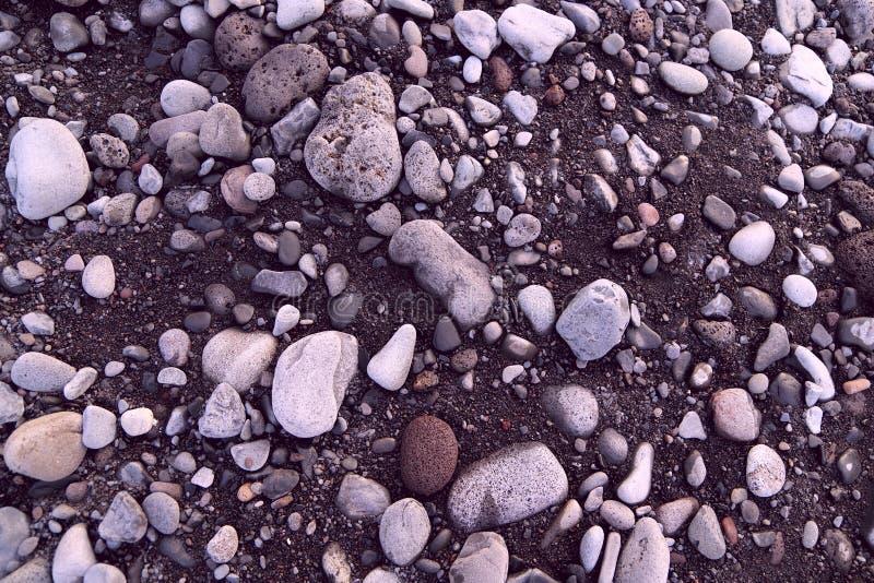 Hoogste mening over de kiezelstenen van verschillende grootte op het donkere vulkanische zand stock foto