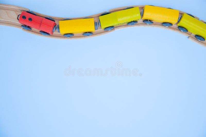 Hoogste mening over de veelkleurige jonge geitjesstuk speelgoed bakstenen van treinauto's op houten spoorweg blauwe achtergrond C royalty-vrije stock foto's