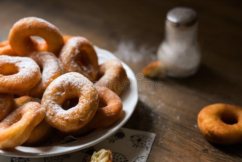 Hoogste mening over een bos van verse eigengemaakte donuts (doughnuts) op een witte plaat, met suikerkom, deegrol stock foto's
