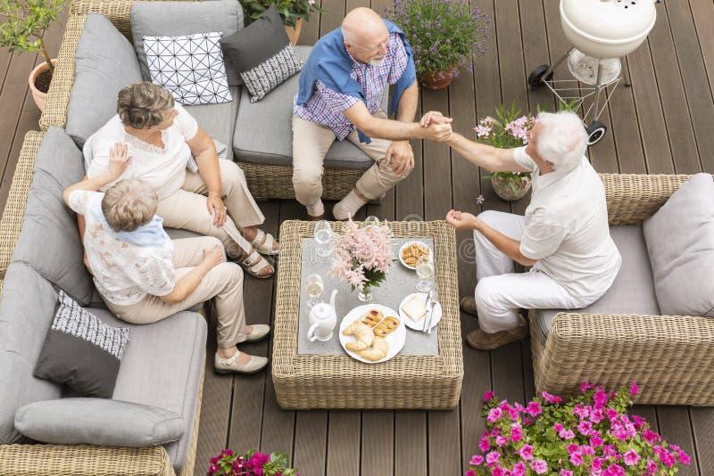 Hoogste mening over hogere mensen die tijdens vergadering over het terras spreken stock afbeelding