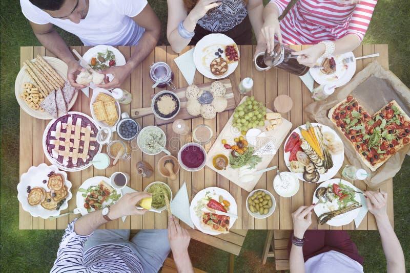 Hoogste mening over mensen die voedsel eten tijdens grillpartij in de tuin stock afbeelding