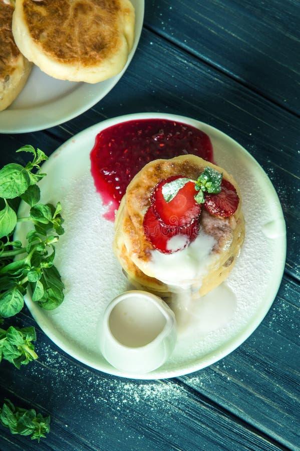 Hoogste mening Sluit omhoog De rustieke die pannekoeken van de ontbijtkaas, met room worden en met aardbeien worden verfraaid geg royalty-vrije stock afbeeldingen