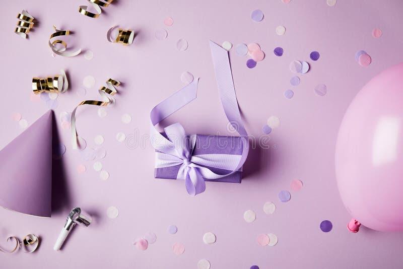 hoogste mening van één violette huidige doos, ballon, partijhoed en confettienstukken op oppervlakte royalty-vrije stock afbeelding