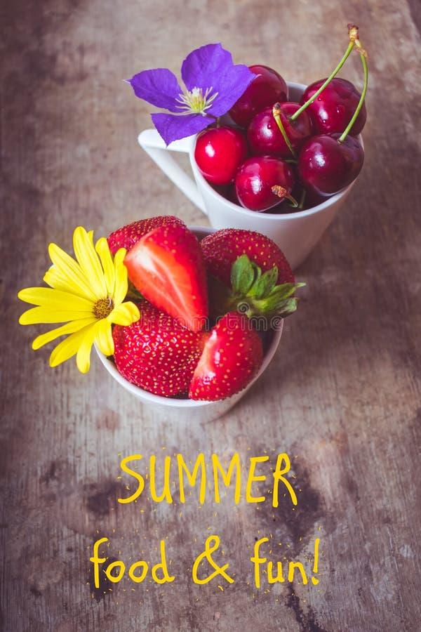Hoogste mening van aardbeien, kersen en gele en purpere bloemen in kommen op houten achtergrond, de Zomervoedsel en pret stock afbeelding