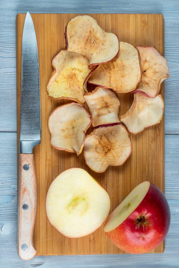 Hoogste mening van appelspaanders en vers-besnoeiingsappel met het mes op een houten achtergrond Blauwe hemel, kalme wateren royalty-vrije stock fotografie