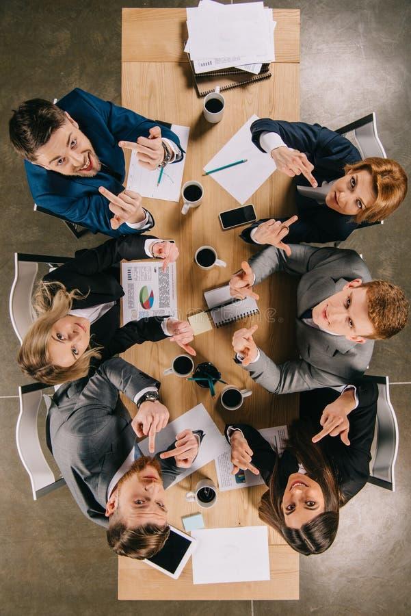 Hoogste mening van bedrijfscollega's die middelvingers tonen en bij lijst zitten stock fotografie