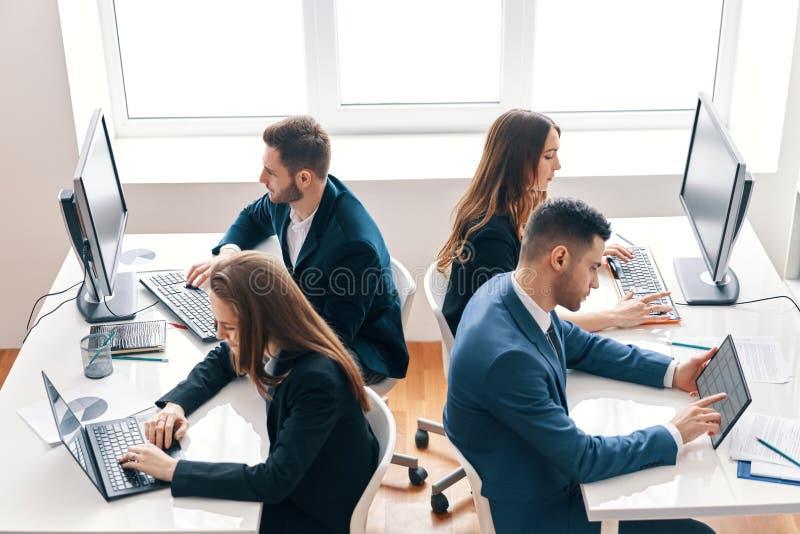Hoogste mening van bedrijfsmensen die aan computer in modern bureau werken stock foto