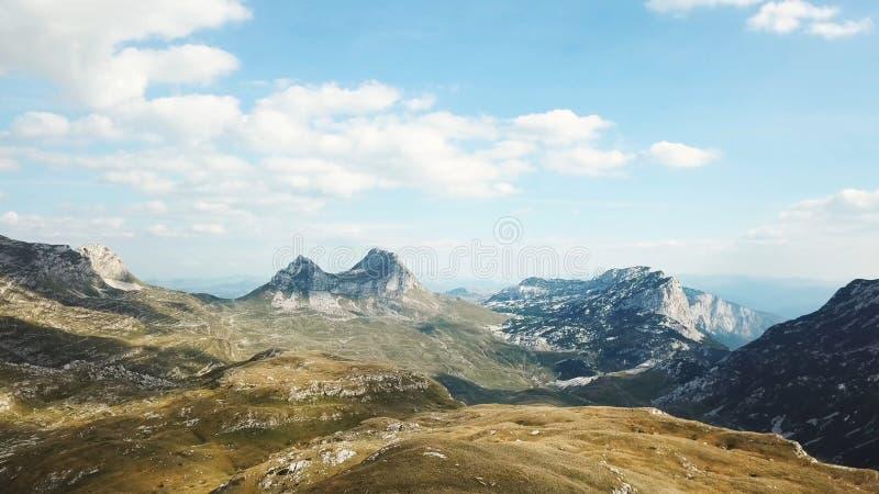 Hoogste mening van bergpanorama tegen blauwe hemel voorraad De rotsachtige pieken van bergen met dekking van gras bij uitlopers l stock foto's