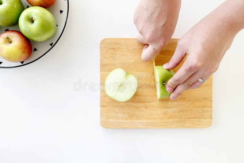 Hoogste mening van Besnoeiings groene appel in de helft met handen door plastic mes in houten hakbord royalty-vrije stock foto