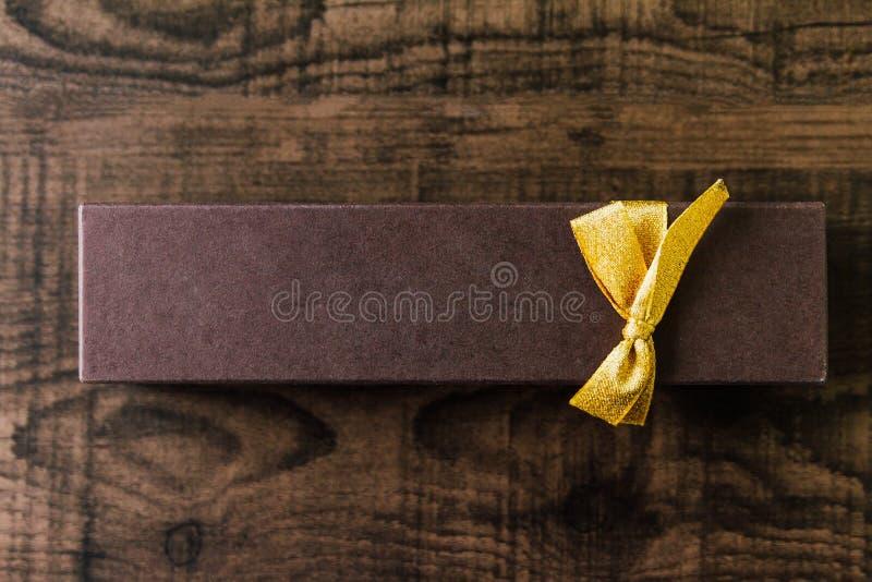 Hoogste mening van bruin het document van de rechthoekchocolade vakje die band met gouden lint op houten achtergrond royalty-vrije stock fotografie