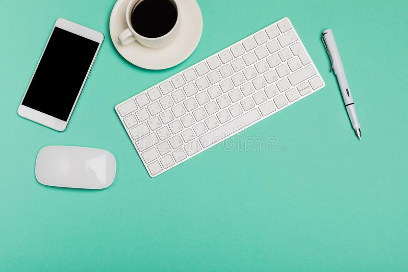 Hoogste mening van bureauwerkruimte met smartphone, toetsenbord, koffie en muis op blauwe achtergrond met exemplaar ruimte, grafi stock fotografie