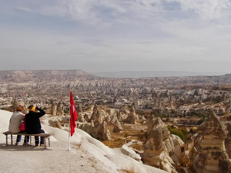 Hoogste mening van Cappadocia twee vrouwen zitten op bovenkant en bekijken de stad stock foto