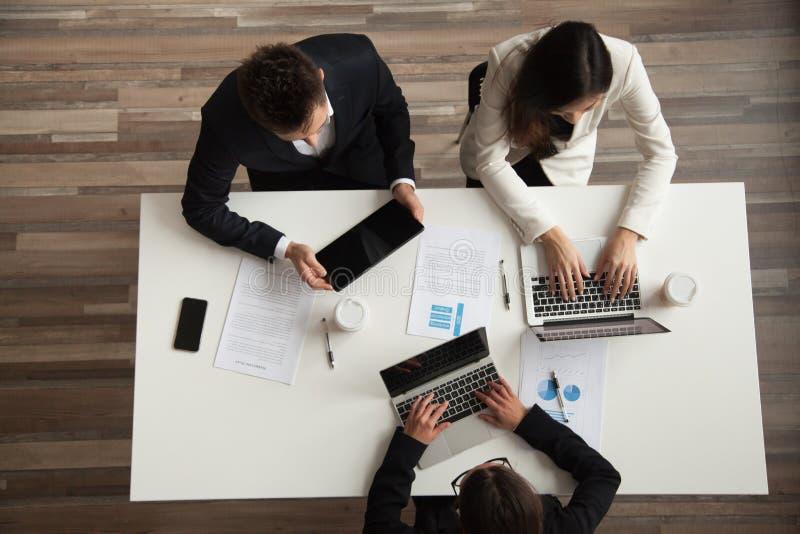 Hoogste mening van collega's die bij laptops in bureau werken stock fotografie