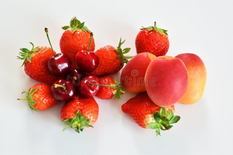 Hoogste mening van de geassorteerde vruchten kersen van de aardbeienabrikoos op een witte achtergrond stock foto