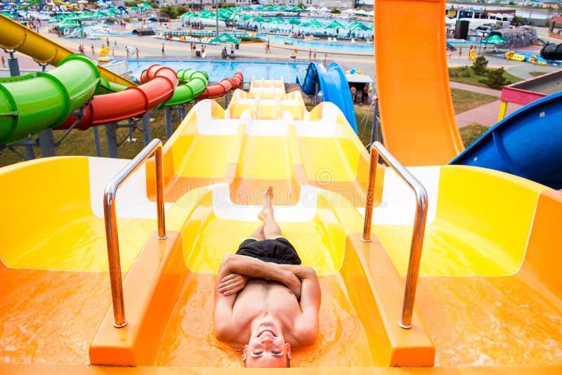Hoogste mening van de gelukkige gekke mens bovenop dia in aquapark - Jongeren die pret in de zomervakantie hebben - Vakantie stock foto