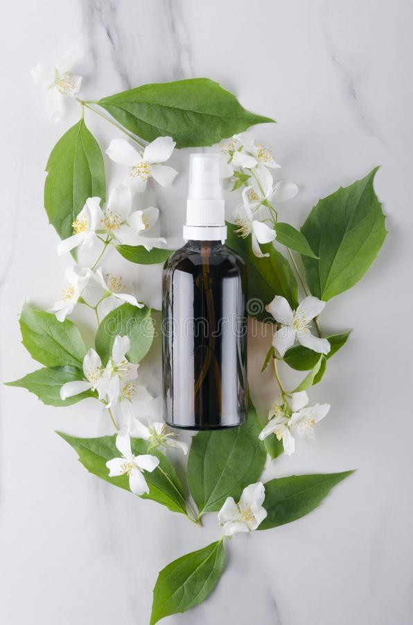 Hoogste mening van van de glasfles en jasmijn bloemen op de witte oppervlakte Concept schoonheidsbehandelingen met jasmijnolie royalty-vrije stock afbeelding
