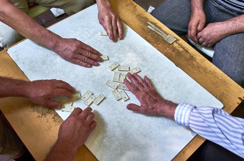 Hoogste mening van de handen van mensen die domino's spelen stock afbeelding