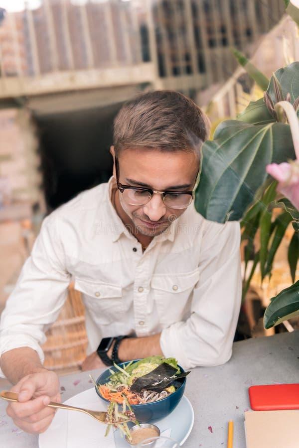 Hoogste mening van de knappe mens die glas dragen die heerlijke avocadosalade eten stock foto