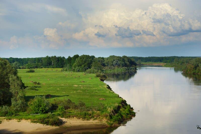 Hoogste mening van de kust van de rivier met groen gras en geoogste hooibergen, bewolkte hemel royalty-vrije stock foto's